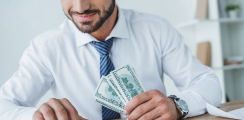 Businessman in suit and tie holding cash in his hand.