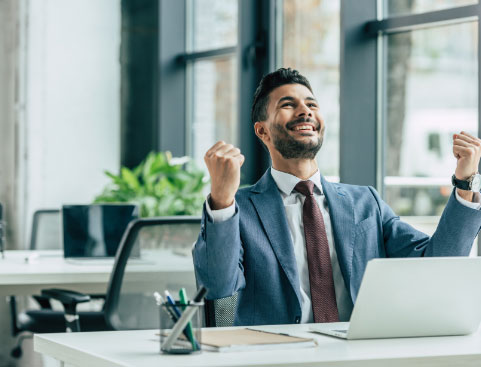 Excited businessman sitting at his desk in front of his laptop