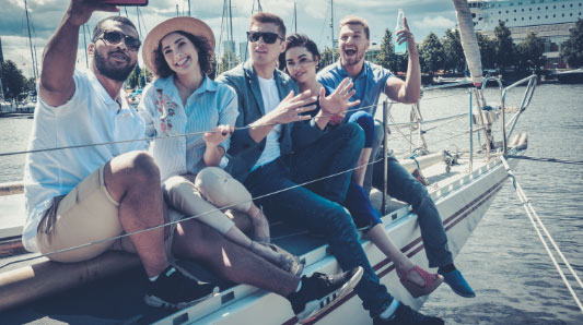 Group of friends sitting on the side of a boat taking a selfie