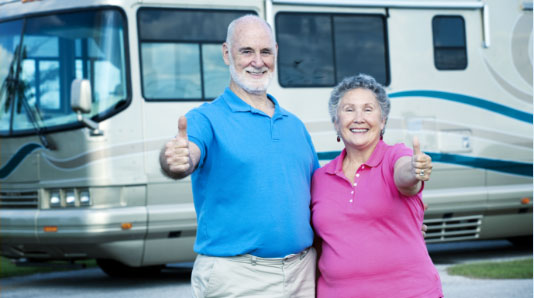 Couple standing in front of RV with their thumbs up