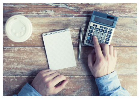 Shot of calculator, notepad, pen, and coffee on a wooden table