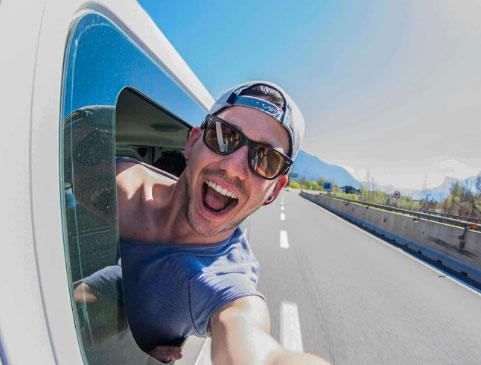 Smiling man in hat and sunglasses sticking his head out the side of an RV